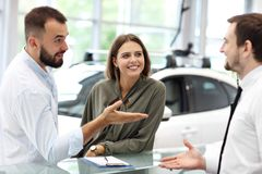 Confident young salesman explaining car features to the young attractive owners. Picture of confident young salesman explaining all the car features to the young stock image