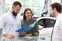 Confident young salesman explaining car features to the young attractive owners royalty free stock photos