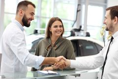 Confident young salesman explaining car features to the young attractive owners stock photos
