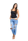 Confident young sexy beauty with hands in pockets looking at camera. Royalty Free Stock Photos