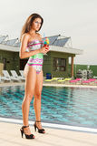 Confident young sexy girl holding cocktail. Beautiful young sexy  girl standing on pool side holding fresh cocktail drink having hot black heels Royalty Free Stock Images