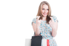 Confident young smiling shopaholic holding fingers crossed Royalty Free Stock Images