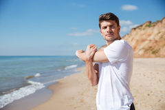 Confident young sportsman doing exercises on the beach Royalty Free Stock Image