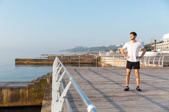 Confident young spotrsman standing on pier royalty free stock photo