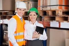 Confident Young Supervisors At Warehouse. Portrait of two confident young supervisors with book standing at warehouse Royalty Free Stock Photos