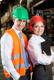 Confident Young Supervisors At Warehouse. Portrait of two confident young supervisors standing at warehouse Royalty Free Stock Photography