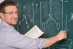 Confident young teacher and classic chalkboard background. Royalty Free Stock Image