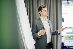 Confident young team leader or manager standing in front of a flip chart and present project on office stock images