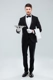 Confident young waiter in tuxedo standing and holding tray. Full length of confident young waiter in tuxedo standing and holding tray stock photo