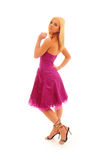 Confident Young Woman. Young confident woman with blonde hair wearing a bright purple party dress on a white background stock photography