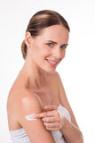 Confident young woman applying cream Royalty Free Stock Image