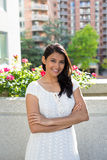 Confident young woman. Closeup portrait, happy confident successful pretty young woman in white dress with arms crossed folded, isolated background of building Royalty Free Stock Photos
