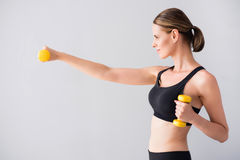 Confident young woman with dumb bells. Be engaged in sport. Content and cheerful young woman holding dumb bells in hands while standing on isolated grey Stock Photos