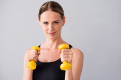 Confident young woman with dumb bells. Strong one. Happy and merry young woman holding dumb bells in hands while standing on isolated grey background Royalty Free Stock Image