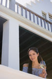 Confident young woman holding white wine glass in balcony at restaurant Royalty Free Stock Image