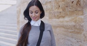 Confident young woman leaning against wall stock video footage