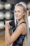 Confident Young Woman Lifting Dumbbell In Gym Royalty Free Stock Image