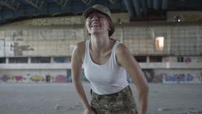 Confident young woman in military uniform training in dusty dirty abandoned building. Slim girl running up to the camera. Young woman in military uniform stock video