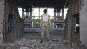 Confident young woman in military uniform walking slowly in dusty dirty abandoned building. Warrior woman in a deserted. Attractive young woman in military stock video footage