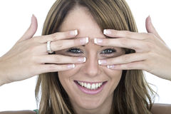 Confident Young Woman Peering Through Fingers Stock Images