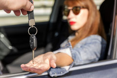 Confident young woman receiving the keys of car. Confident young woman receiving the keys of her new car Royalty Free Stock Photography