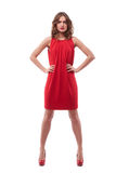 Confident young woman in red dress with hands on hips stock photo