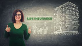 Life insurance. Confident young woman showing thumbs up positive gesture over blackboard background with a flat house and happy family sketch. Life insurance and royalty free illustration