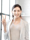 Confident young woman showing v-sign Royalty Free Stock Images