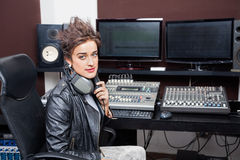Confident Young Woman Sitting At Mixing Desk Stock Photography