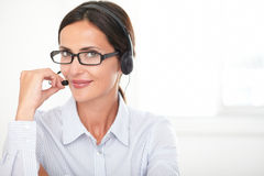 Confident young woman speaking on headphones Stock Images
