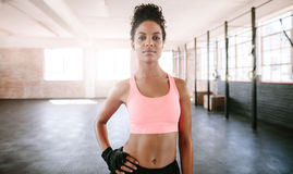 Confident young woman standing in gym Royalty Free Stock Image