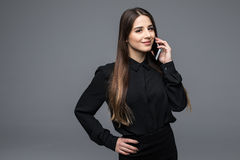 Confident young woman talking on the mobile phone while standing against grey background Royalty Free Stock Image