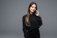 Confident young woman talking on the mobile phone while standing against grey background Stock Photography