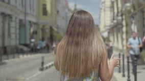 Confident young woman walking around the old european city, talking on the phone, waving her arms. Leisure of happy girl. Confident young woman walking around stock footage
