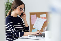 Confident young woman working in her office with laptop. Stock Photography