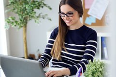 Confident young woman working in her office with laptop. Portrait of confident young woman working in her office with laptop Royalty Free Stock Photo