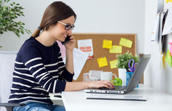 Confident young woman working in her office with laptop. Portrait of confident young woman working in her office with laptop Stock Image