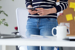 Confident young woman working in her office with mobile phone. Portrait of confident young woman working in her office with mobile phone Royalty Free Stock Image