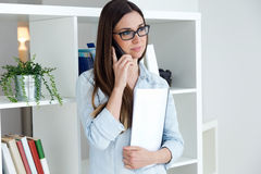 Confident young woman working in her office with mobile phone. Stock Photo