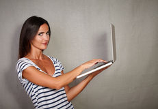 Confident youngster browsing laptop while smiling Royalty Free Stock Image