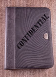 Confidential. Gray folder over wooden background, with text Confidential over it Royalty Free Stock Images