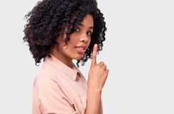 African American young woman dressed in pink shirt holding index finger on lips, asking to keep silence over white wall. Confidential African American young stock image
