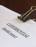 Confidential business. A confidential special report, held together with a large paper clip, on a dark brown table Stock Photo