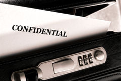 Confidential Classified Document in Briefcase. Confidential document letter sticking out of a little ajar open briefcase during a top secret classified