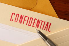 Confidential contents. Confidential document held in a folder with a pen pointing at the confidential stamp