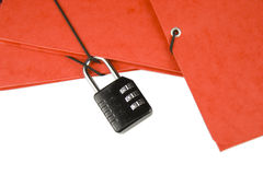 Confidential Files. A black number lock attached to red paper files - symbol of confidentiality and security - isolated on white Royalty Free Stock Photo