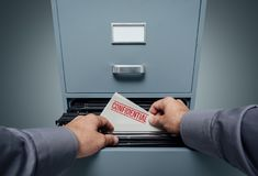 Confidential information and privacy. Office clerk searching for files in the filing cabinet, he finds a folder with confidential information inside, personal Royalty Free Stock Photos