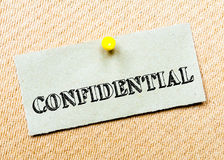 Confidential Message. Recycled paper note pinned on cork board.Confidential Message. Concept Image Stock Image