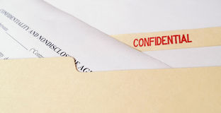 Confidential Non-Disclosure Agreement. A legal confidentiality and non-disclosure agreement in a manila folder marked Confidential Stock Photos