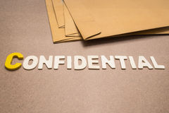 Confidential wording on brown background. With pile of brown envelope in the background Royalty Free Stock Photo